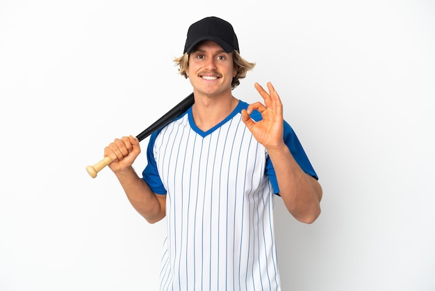 Junger blonder mann isoliert auf weißem hintergrund, der baseball spielt und ein ok-zeichen mit den fingern zeigt