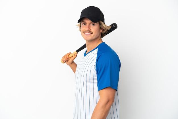 Junger blonder mann lokalisiert auf weißem hintergrund, der baseball spielt