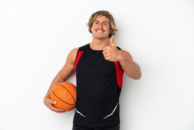Junger blonder mann lokalisiert auf weißem hintergrund, der basketball und mit daumen oben spielt
