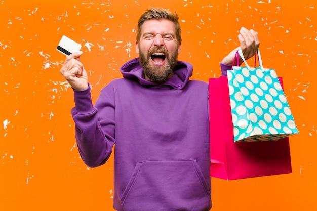 Junger blonder mann mit den einkaufstaschen, die einen purpurroten hoodie gegen schädigende orange wand tragen