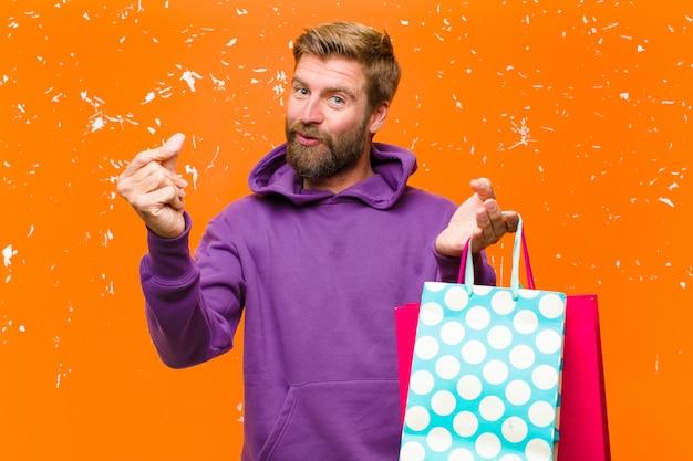 Junger blonder mann mit den einkaufstaschen, die einen purpurroten hoodie tragen, schädigte orange wand