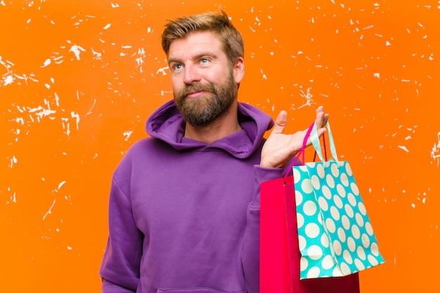 Junger blonder mann mit den einkaufstaschen, die einen purpurroten hoodie tragen