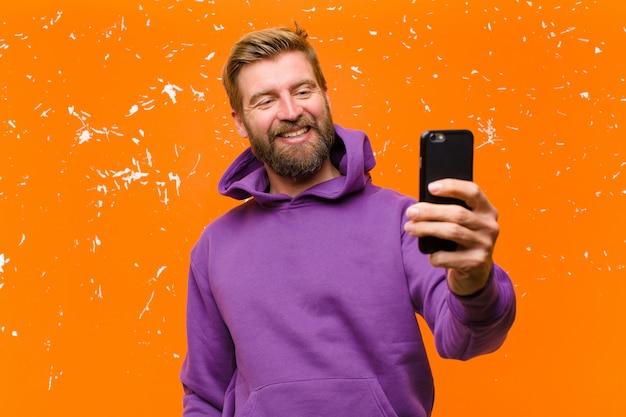 Junger blonder mann mit einem intelligenten telefon, das einen purpurroten hoodie gegen schädigende orange wand trägt