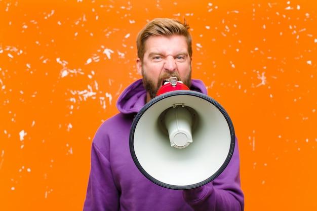 Junger blonder mann mit einem megaphon, das einen purpurroten hoodie gegen schädigende orange wand trägt