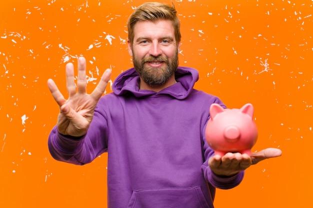Junger blonder mann mit einem sparschwein, das einen purpurroten hoodie gegen schädigende orange wand trägt
