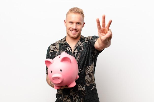 Junger blonder mann mit einem sparschwein, das nummer eins oder zuerst mit der hand vorwärts zeigt