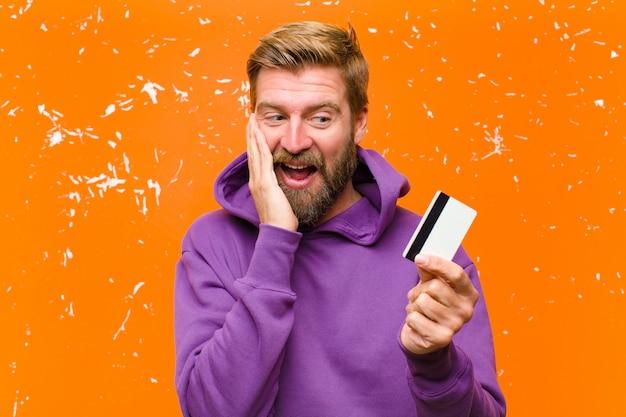 Junger blonder mann mit einer kreditkarte, die einen purpurroten hoodie gegen schädigende orange wand trägt