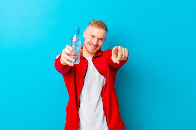 Junger blonder mann mit einer wasserflasche, die sportkleidung trägt