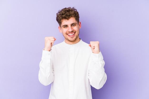 Junger blonder mann mit lockigem haar, der einen sieg, leidenschaft und begeisterung, glücklichen ausdruck feiert