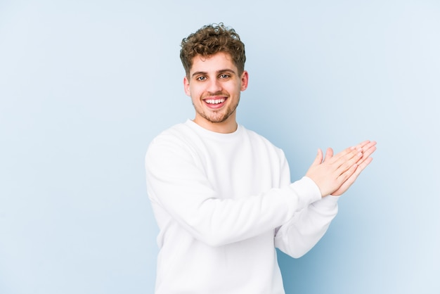 Junger blonder mann mit lockigem haar, der sich energisch und bequem fühlt und sich selbstbewusst die hände reibt