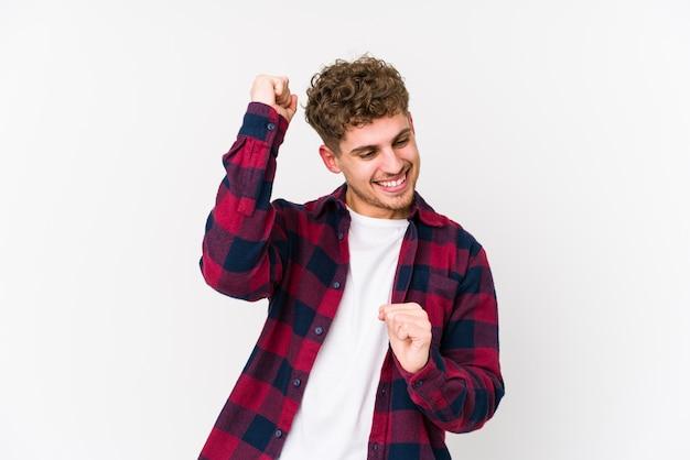 Junger blonder mann mit lockigem haar, der tanzt und spaß hat