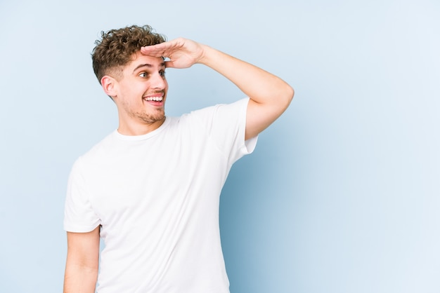 Junger blonder mann mit lockigem haar, der weit weg schaut und hand auf stirn hält