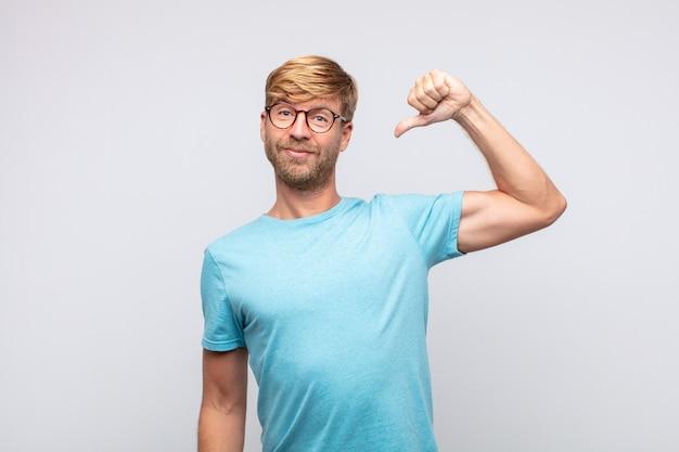 Junger blonder mann mit stolzem gesichtsausdruck, auf sich selbst zeigend
