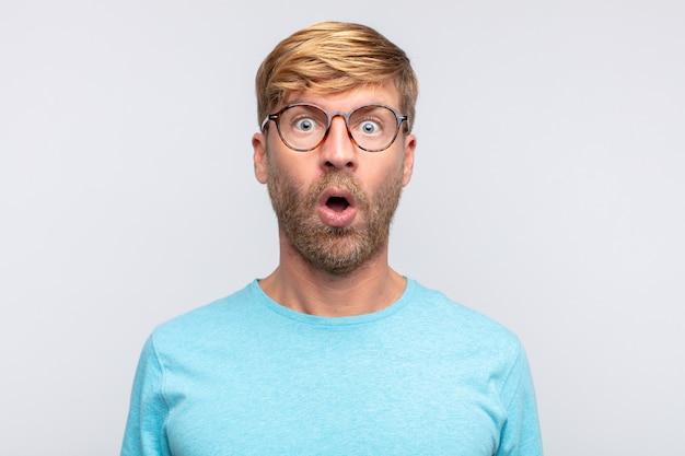 Junger blonder mann überrascht oder geschockt