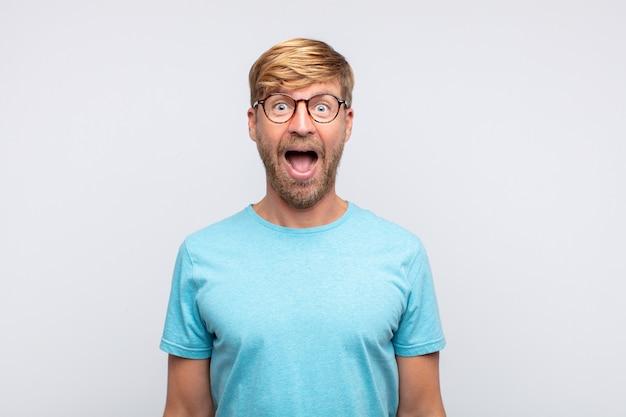 Junger blonder mann überrascht oder schockiert