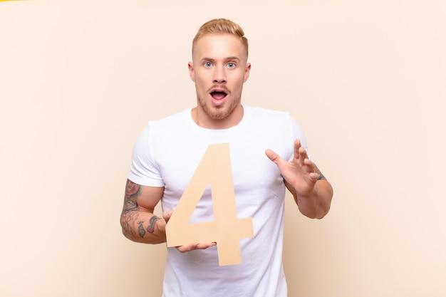 Junger blonder mann überrascht, schockiert, erstaunt, eine nummer 4 haltend