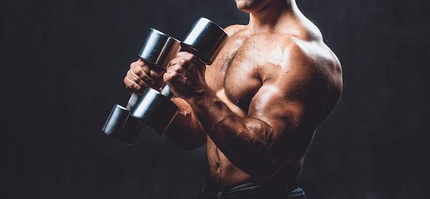 Junger bodybuilder auf einem schwarzen hintergrund