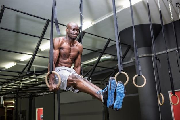 Junger bodybuilder, der sich auf und ab anhebt