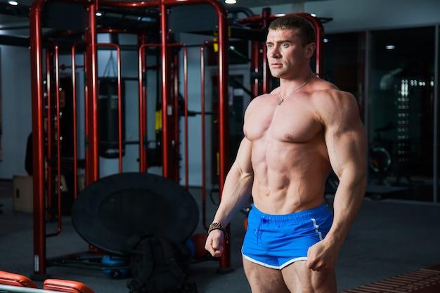 Junger bodybuilder, der starken muskelkörper im fitnessstudio demonstriert. fit mann posiert im sportverein