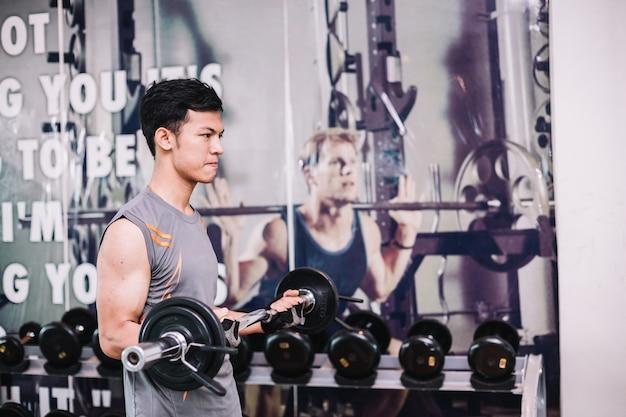Junger bodybuilder trainiert, indem er einen dummkopf in der turnhalle anhebt.