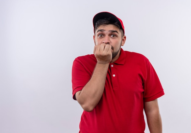 Junger bote in roter uniform und gestresster mütze und nervösen beißenden nägeln