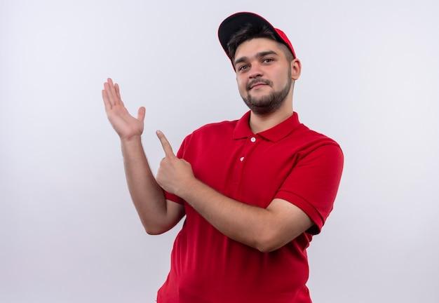 Junger bote in roter uniform und lächelnder mütze, die mit zeigefinger auf seinen arm zeigt