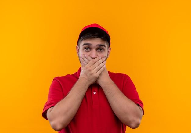 Junger bote in roter uniform und mütze schockiert, mund mit händen bedeckend