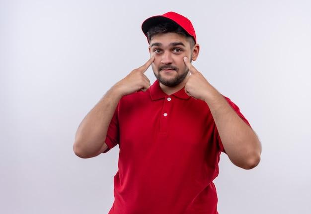 Junger bote in roter uniform und mütze zeigt auf seine augen und wartet auf zahlung