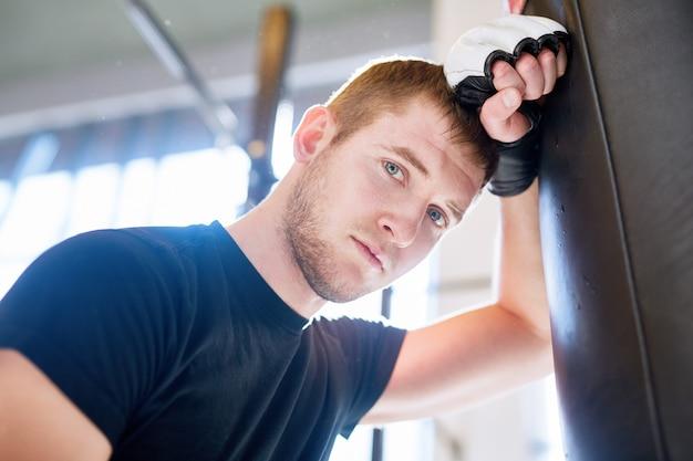 Junger boxer, der auf sandsack sich lehnt