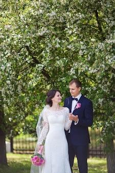 Junger bräutigam und braut mit rosa hochzeitsstrauß im blühenden garten