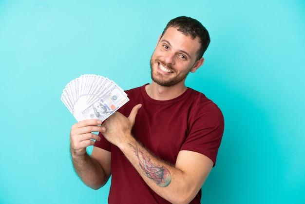 Junger brasilianischer mann, der stolz und selbstzufrieden viel geld auf isoliertem hintergrund nimmt