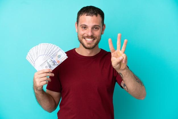 Junger brasilianischer mann, der viel geld über isoliertem hintergrund nimmt, glücklich und zählt drei mit den fingern count