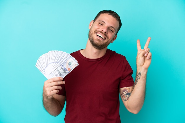 Junger brasilianischer mann, der viel geld über isoliertem hintergrund nimmt und lächelt und victory-zeichen zeigt