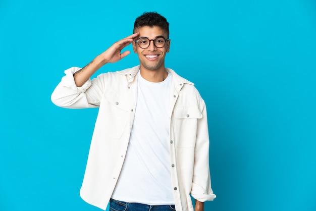 Junger brasilianischer mann lokalisiert auf blauer wand, die mit hand mit glücklichem ausdruck salutiert