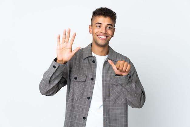 Junger brasilianischer mann lokalisiert auf weißer wand, die sechs mit den fingern zählt