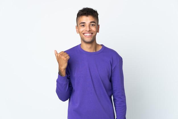 Junger brasilianischer mann lokalisiert auf weißer wand, die zur seite zeigt, um ein produkt zu präsentieren