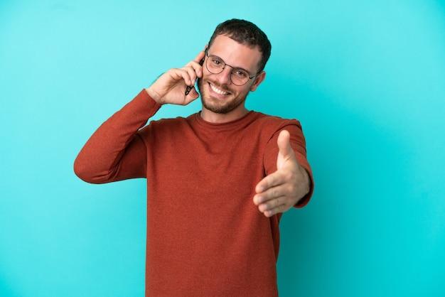 Junger brasilianischer mann mit handy isoliert auf blauem hintergrund händeschütteln für den abschluss eines guten deals