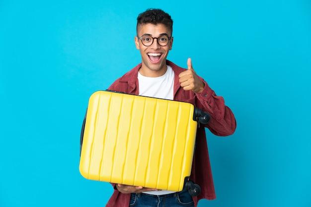 Junger brasilianischer mann über isolierter wand im urlaub mit reisekoffer und mit daumen nach oben