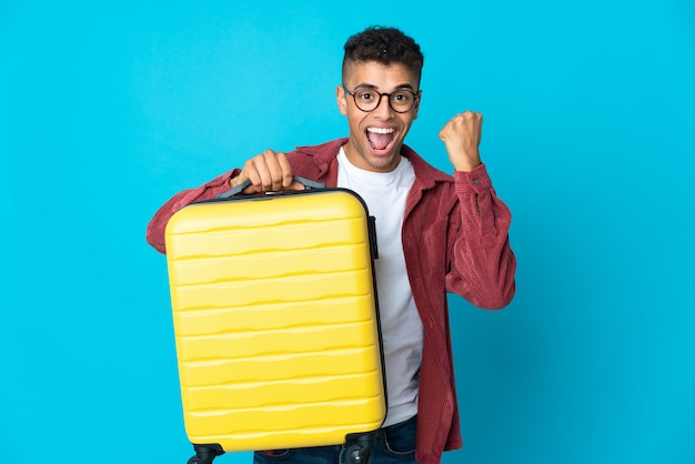 Junger brasilianischer mann über isolierter wand im urlaub mit reisekoffer