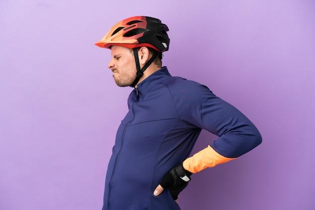 Junger brasilianischer radfahrer, isoliert auf violettem hintergrund, der an rückenschmerzen leidet, weil er sich angestrengt hat?