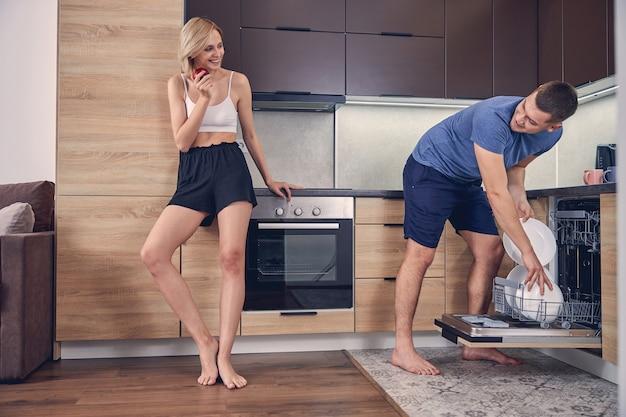 Junger brünette mann, der teller in die spülmaschine stellt, während er eine blonde frau sieht, die roten apfel isst