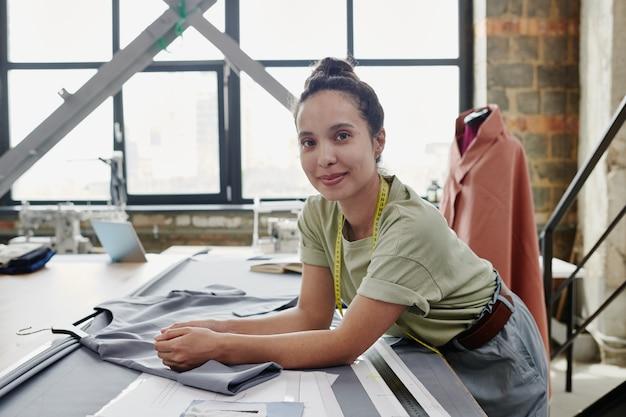 Junger brünetter schneider oder designer von kleidern, die auf tisch mit unvollendetem kleid, textil, papiermustern und lineal während der arbeit lehnen