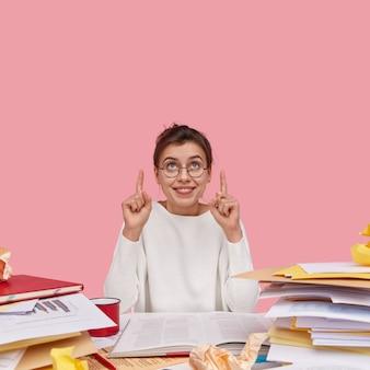 Junger brünetter student, der am schreibtisch mit büchern sitzt