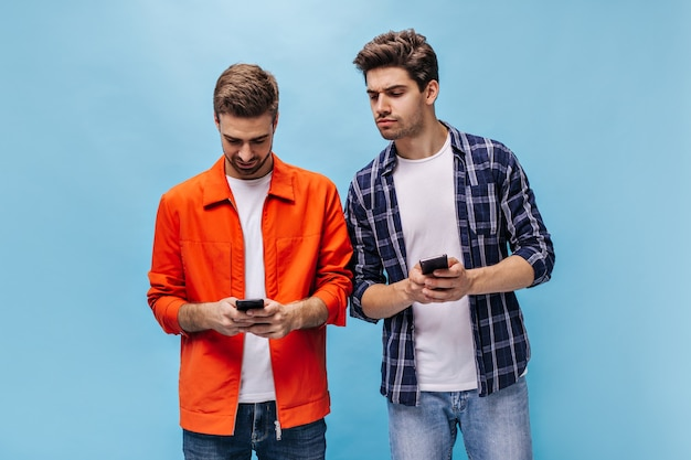 Junger brunet-mann im karierten hemd versucht, auf dem telefonbildschirm seiner freunde zuzusehen. bärtiger kerl in orangefarbener jackenhaltung an blauer wand.