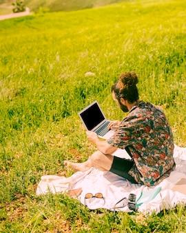 Junger brunetmann, der laptop auf natur hält