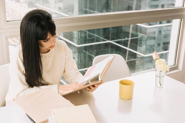 Junger brunette, der bei tisch liest