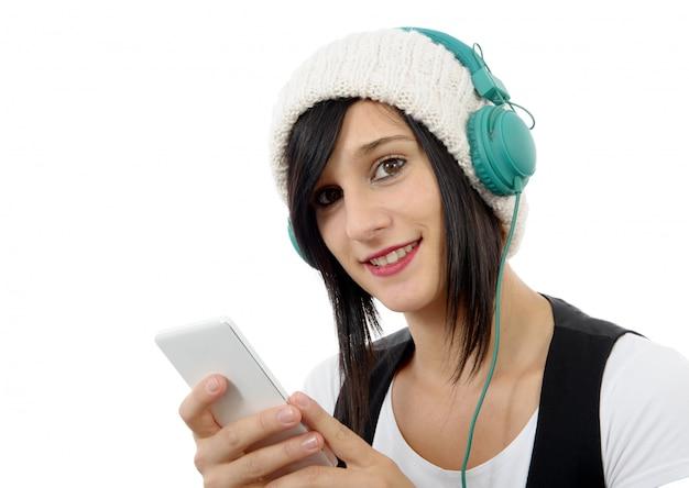 Junger brunette, der musik mit kopfhörern und telefon hört