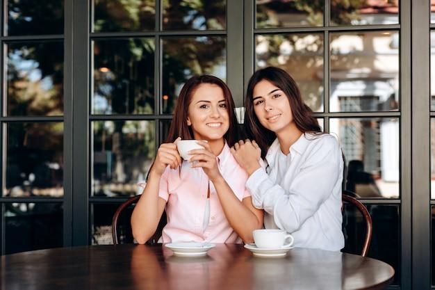 Junger brunette, der schön in trinkendem kaffee des cafés aufwirft