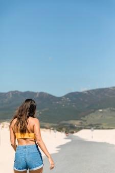 Junger brunette gegen berge im sonnenlicht
