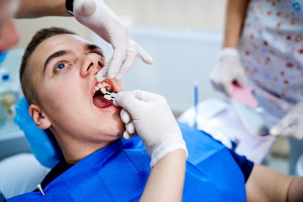 Junger brunettemann, der eine zahnmedizinische behandlung empfängt. zahnarzthände in den weißen medizinischen handschuhen.